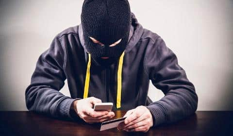 hacker using phone and card